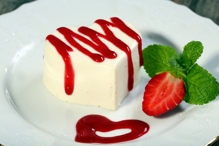 Panna cotta in the shape of a heart with cherry sauce  photo
