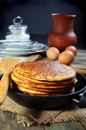 Oatmeal pancakes in frying pan on a wooden table   Stock Photo