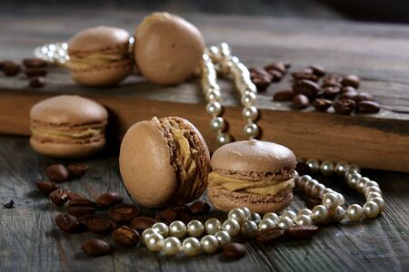 Almond cakes, coffee beans and pearls on a wooden table  photo