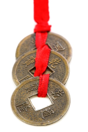 Three Chinese coins tied with red ribbon on a white background