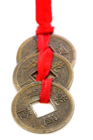 Trzy chińskie monety związane z czerwoną wstążką na białym tle Zdjęcie Seryjne