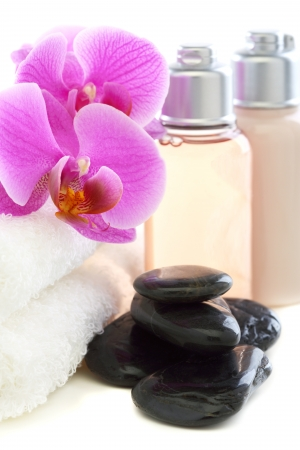 Cosmetics and towels with pink orchid on a white background  photo