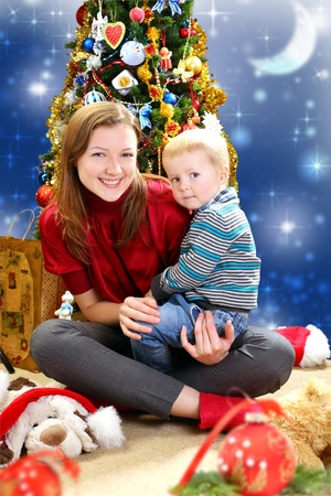 Beautiful young woman with a child on the background of the Christmas tree Stock Photo - 21638480