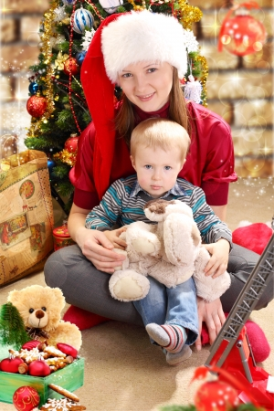 Young woman in a Santa hat and little boy near Christmas tree Stock Photo - 21638482