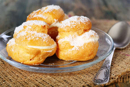 choux bun: Eclairs in glass saucer on a wooden table.