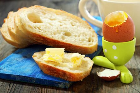 Soft-boiled egg and bread with butter on a wooden table. photo