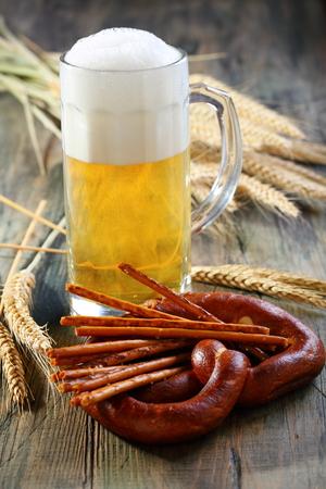 pretzel stick: Pretzel, salty sticks and glass of beer on a wooden table.