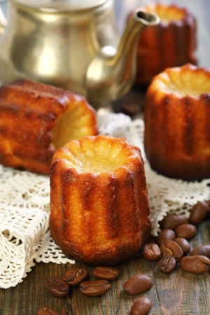 Cake canneles and old coffee pot on wooden table.