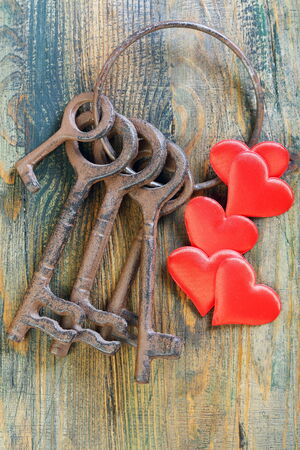 objec: Bunch of old keys and red hearts on a wooden board.