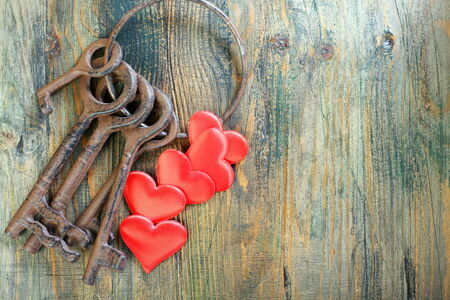 Bunch of old keys and red hearts on a wooden board. photo