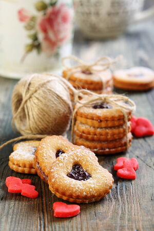 Biscuits and marzipan red hearts on a wooden table. photo