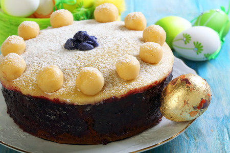 Easter cake with marzipan on blue wooden table.