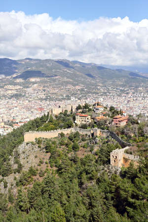 Old fortress on the mountain and the modern city of Alanya.  photo