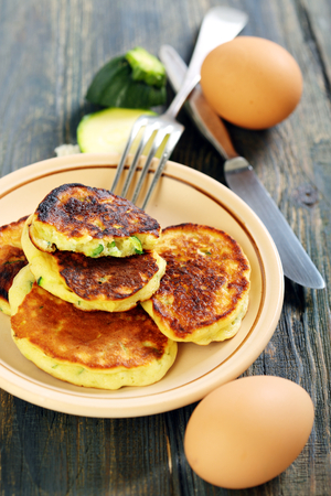 Plate with Zucchini fritters; fork and knife on a wooden table. photo