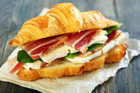 Croissant with ham and brie cheese on white parchment. Stock Photo
