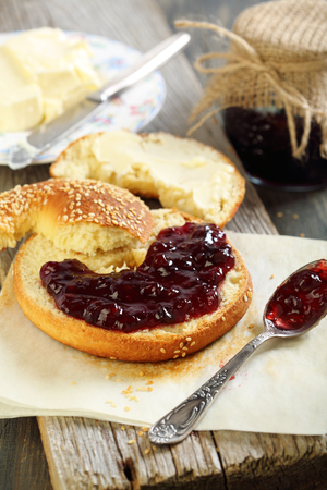 Homemade bagel with jam and butter on the old table.