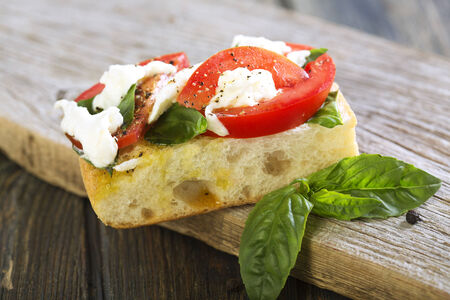 Sandwich with tomatoes, basil and mozzarella on wooden board. photo