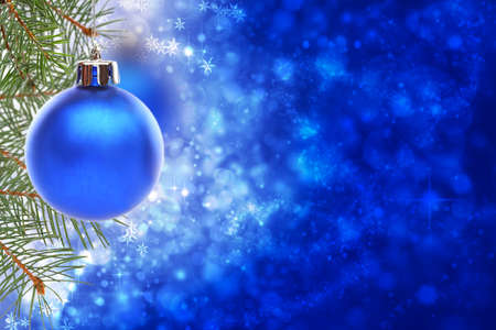 Christmas ball and spruce branches on a blurred blue shiny and sparkling background. photo