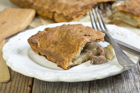 Piece of meat pie with fork and knife on a white plate. photo