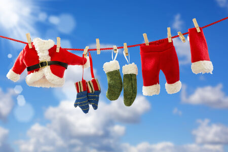 Rope with Santas clothes over blue sky background photo