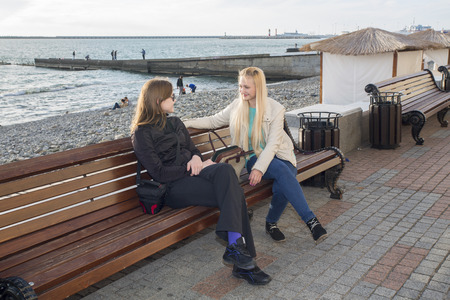lively: Two friends sitting in a lively conversation on the bench. Stock Photo