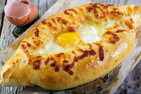 Pie with cheese and egg yolk on an old wooden table. 免版税图像 - 35538695