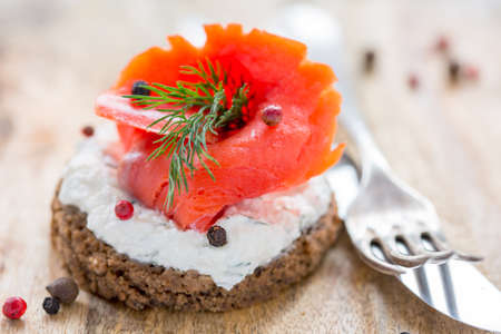 red salmon: Sandwich with salted red salmon and black bread close up.