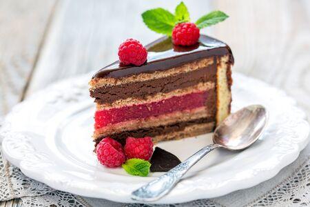 porcion de torta: Piece of cake with raspberry jelly on dessert plate.