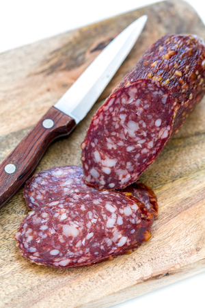 dry sausage: Sliced dry sausage and knife on a white background.