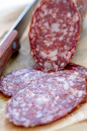 dry sausage: Dry sausage on a wooden board close up.