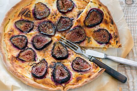 sweet and savoury: Sliced pizza with figs, fork and knife closeup.