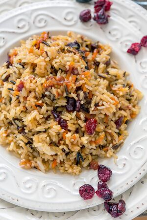 rice plate: Rice with raisins, cranberries and carrots closeup.
