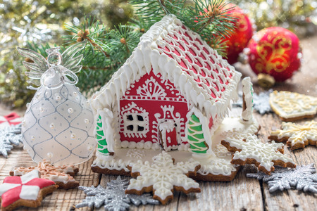 christmas house: Christmas angel and gingerbread house on a wooden table. Stock Photo