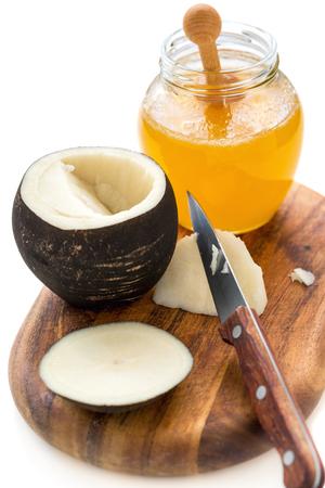 Black radish and a jar of honey on white background.