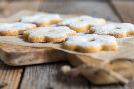 powdered: Cookies in the shape of flowers sprinkled with powdered sugar.