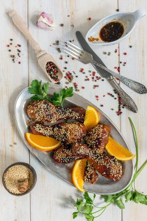 Chicken drumsticks with sesame and orange on a white wooden table. Stock Photo