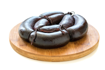 Wooden stand with black pudding on a white background.