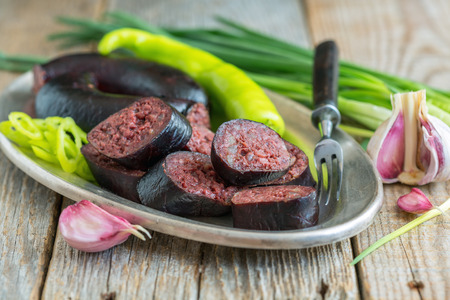 Homemade blood sausage on an old wooden table.