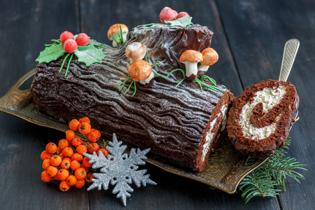 Piece of the traditional Christmas cake, snowflake and red berries on a wooden table. 免版税图像 - 66129831