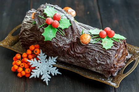 yule: Christmas chocolate yule log with decor of colored chocolate on a wooden table.