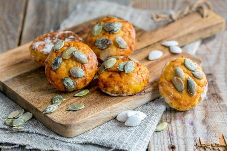 Pumpkin scones with thyme on an old wooden table.