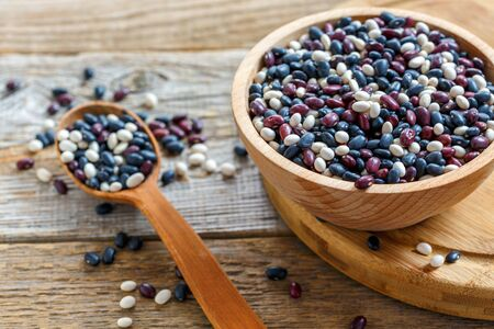 Bowl with red, white and black beans on old wooden table. Stock Photo