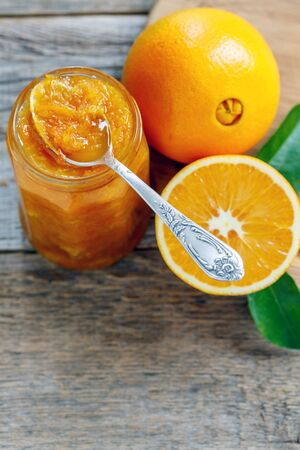 teaspoon: Teaspoon in jar with orange jam on a wooden table. Stock Photo