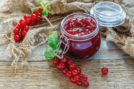 Jar of homemade jam and red currant on wooden table with sacking. Stock Photo
