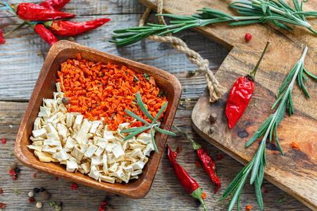 legumbres secas: Secado verduras en un bol, pimienta y romero en una tabla de madera. Foto de archivo
