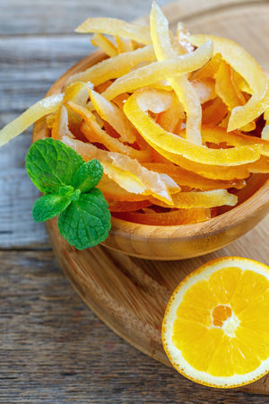 Full bowl of candied orange peel and mint on an old wooden table.