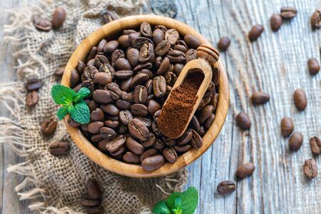 Grains and ground coffee in a wooden bowl on the old sacking. Stock Photo