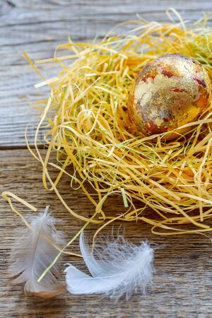 Golden egg in the nest and light feathers on the old wooden background. Stock Photo