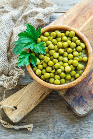 Bowl with canned green peas and sprig of parsley on a wooden cutting board. Stock Photo