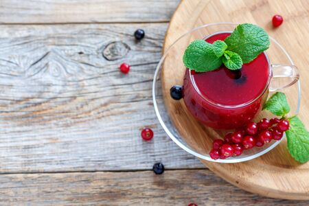 summer pudding: Russian currant kissel and mint in glass cup on an old wooden table.